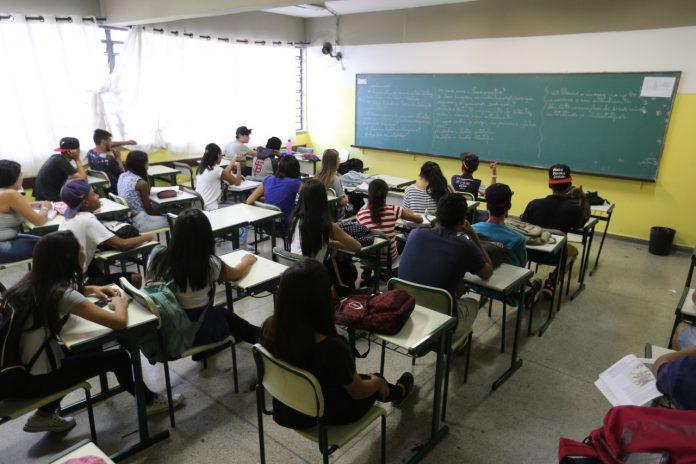 #Pracegover Foto: na imagem há um quadro, alunos, cadeiras e mesas