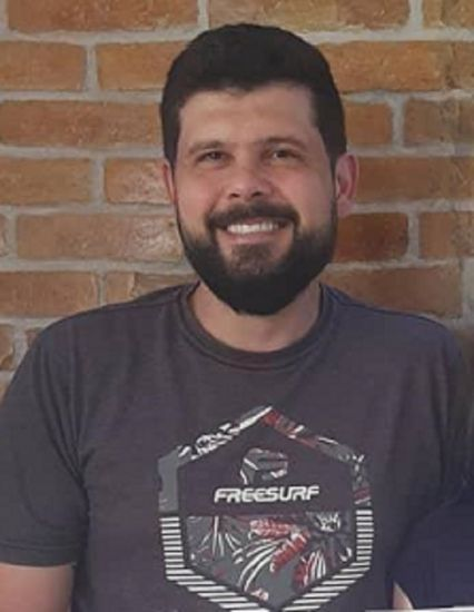 #Pracegover Foto: na imagem há um homem com roupa escura, de barba e sorrindo