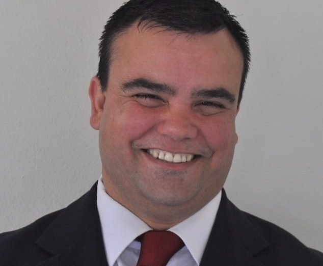 #Pracegover Foto: na imagem há um homem sorridente, de terno preto , camisa branca e gravata bordo