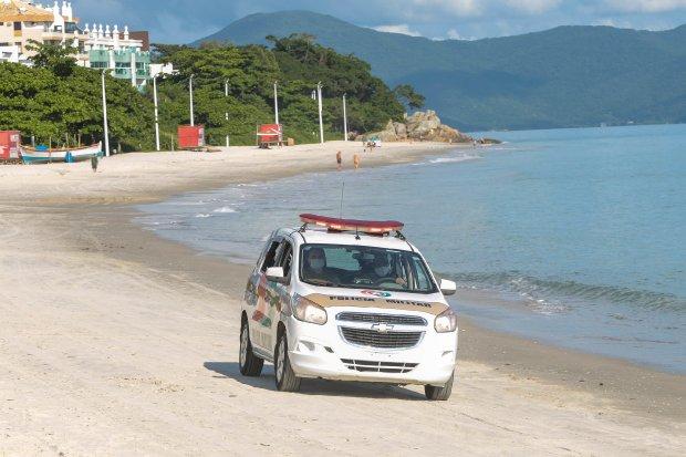 #Pracegover Foto: na imagem há uma viatura da PM, o mar, árvores, bandeiras e a faixa de areia