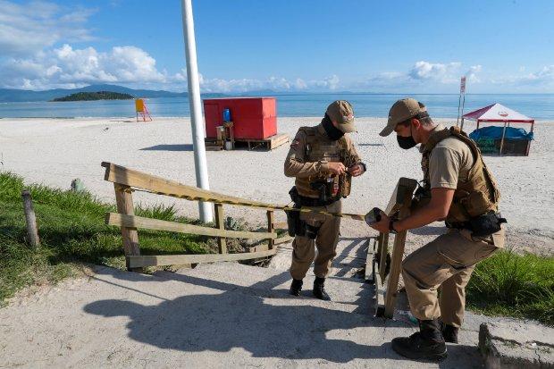 #Pracegover Foto: na imagem há dois homens, o mar, faixa de areia, barracas, calçada