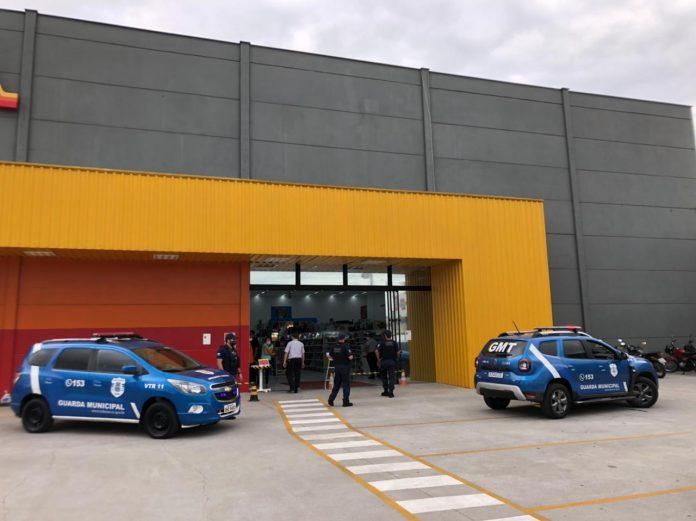 #Pracegover Foto: na imagem há um edifício, carros da GM e pessoas