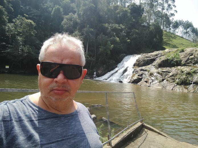 #Pracegover Foto: na imagem há um homem de óculos escuros, árvores e água