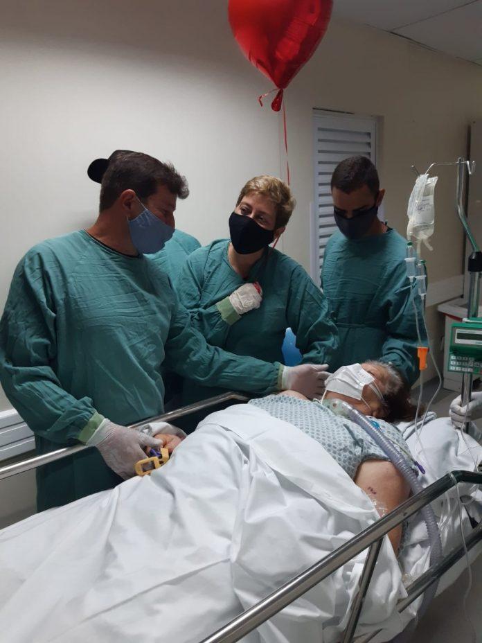 #Pracegover Foto: na imagem há três pessoas em pé e uma deitada na maca de um hospital