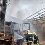#Pracegover Foto: na imagem há um caminhão, dois homens, uma estrutura de madeira e muita fumaça