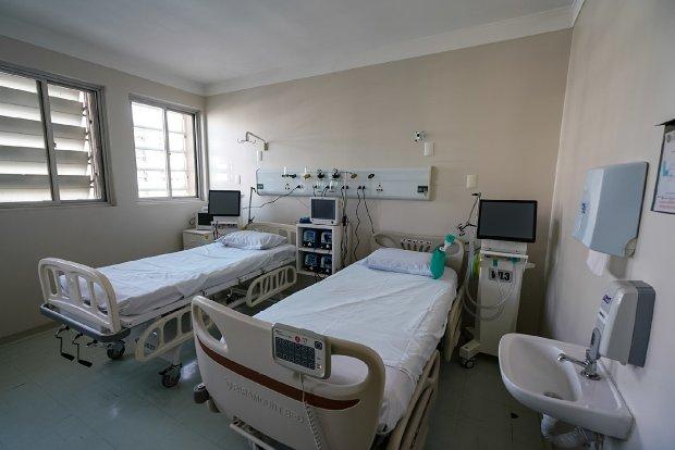 #Pracegover Foto: na imagem há leitos, uma pia de banheiro, saboneteira, porta papel toalha e aparelhos hospitalares