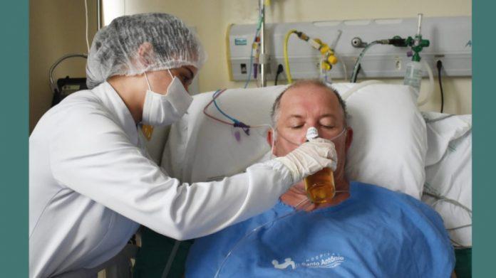#Pracegover Foto: na imagem há um homem deitado em uma maca e uma mulher dando algo de beber para o homem