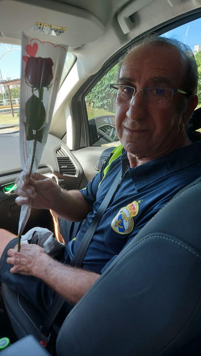 #Pracegover Foto: na imagem há um homem com uma flor na mão. Ele está dentro de um carro