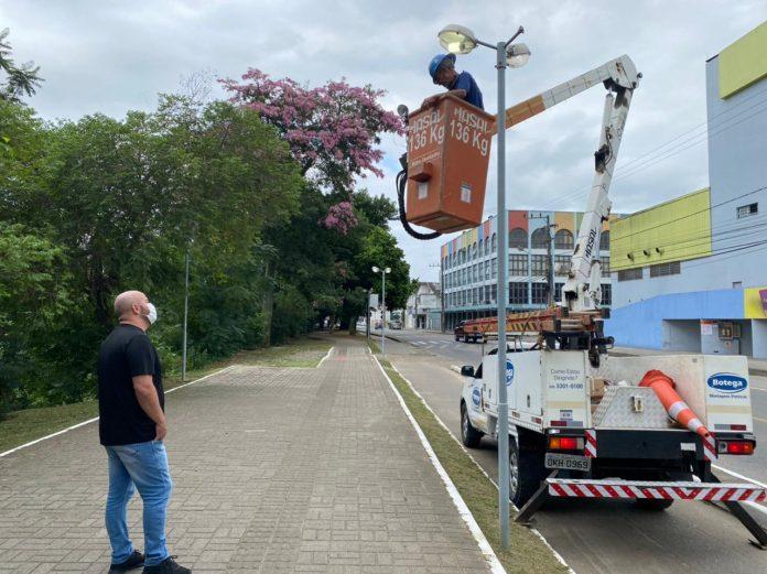 #Pracegover Foto: na imagem há dois homens, um veículo, edifício e árvores