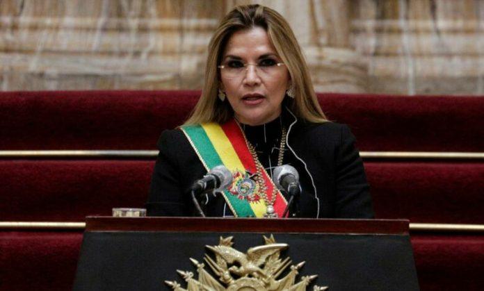 #Pracegover Foto: na imagem há uma mulher com roupa preta e uma faixa presidencial. Há também microfones