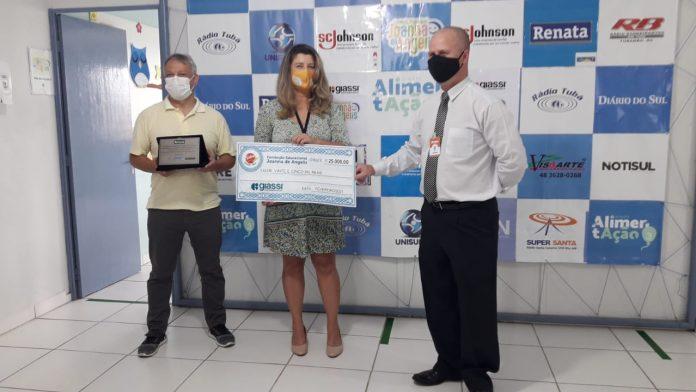 #Pracegover Foto: na imagem há três pessoas. Duas segurando um cheque simbólico e a outra uma placa
