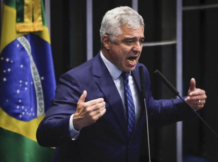 #Pracegover Foto: na imagem há um homem de terno, microfones e a bandeira do Brasil