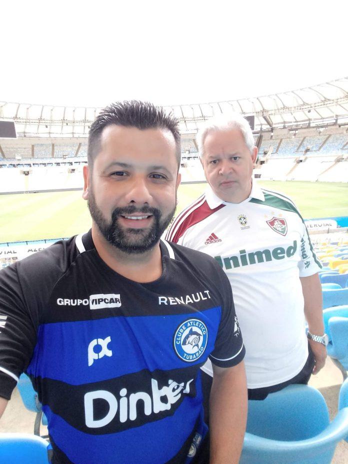 #Pracegover Foto: na imagem há dois homens (filho e pai) e um estágio de futebol