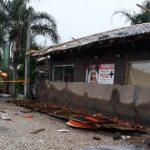 #pracegover Na foto, fachada da pizzaria com a marquise caída e um Bombeiro
