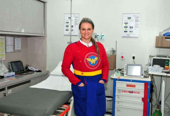 #Pracegover Foto: na imagem há uma mulher com uma roupa de heroína . Ela está em um consultório