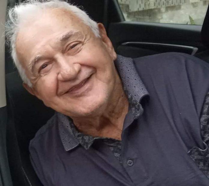 #Pracegover Foto: na imagem há um homem com os cabelos grisalhos, sorridente e com camisa cinza