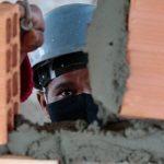 #Pracegover Foto: na imagem há um homem de máscara e capacete, há tijolos e massa de concreto