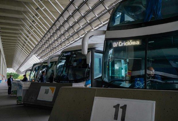 #Pracegover Foto: na imagem há alguns ônibus, pessoas e edificação