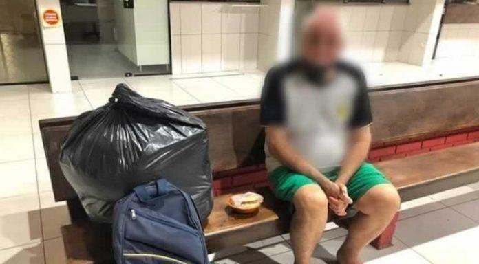 #Pracegover Foto: na imagem há um idoso, um banco, uma mala e uma sacola