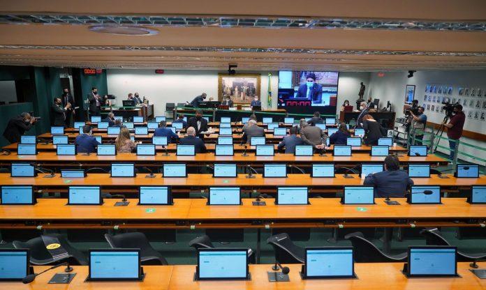 #Pracegover Foto: na imagem há pessoas, computadores, microfones, câmeras e telões