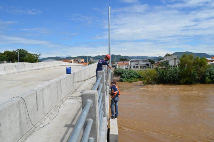 #Pracegover Foto: na imagem há uma ponte de concreto, dois homens, um rio e árvores