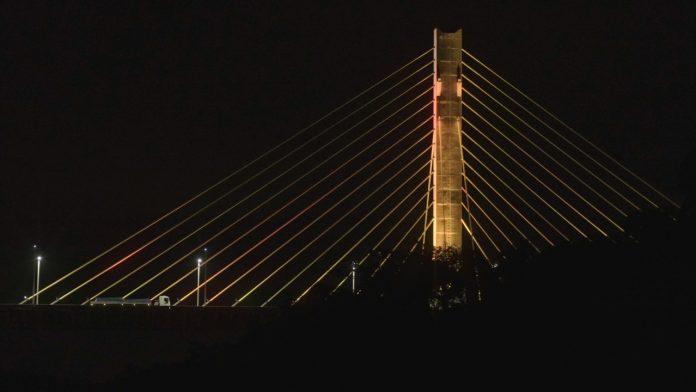 #Pracegover Foto: na imagem há uma ponte iluminada e alguns veículos