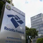 #pracegover Na foto, toten da Receita Federal ao lado de árvores