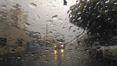 #pracegover Na foto, janela do carro coberta de chuva e ao fundo os faróis de um veículo