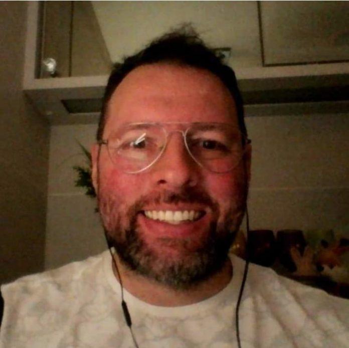 #Pracegover Foto: na imagem há um homem sorridente e com óculos de grau