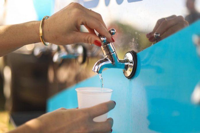 #Pracegover Foto: na imagem há duas mãos, um copo e uma torneira