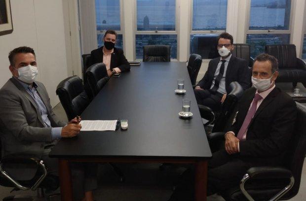 #Pracegover Foto: na imagem há 4 homens, copos, mesa e cadeiras