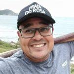 #pracegover Na foto, Rogério esta usando um boné e óculos e sorrindo