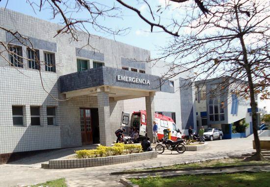 #Pracegover Foto: na imagem há um hospital, plantas, gramado e galhos de árvores