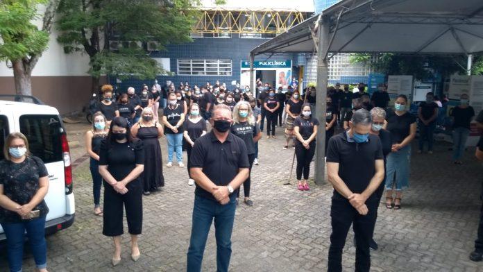 #Pracegover Foto: na imagem há inúmeras pessoas com roupa preta, há carros e um edifício
