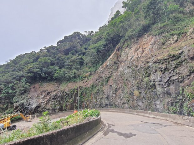 #Pracegover Foto: na imagem há uma via, árvores e rochas