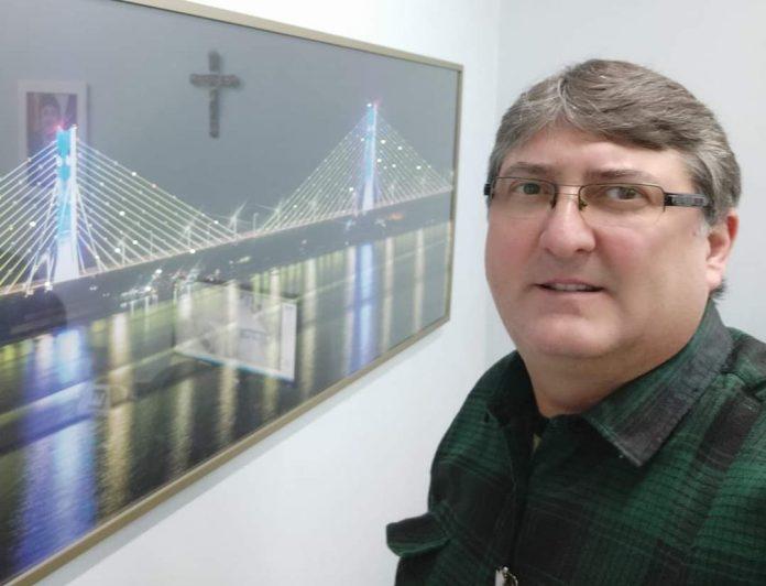 #Pracegover Foto: na imagem há um homem de camisa verde e de óculos