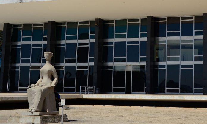 #Pracegover Foto: na imagem há um edifício e uma estátua