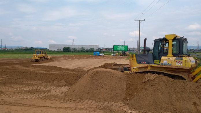 #Pracegover Foto: na imagem há uma máquina, terra, placa e construção