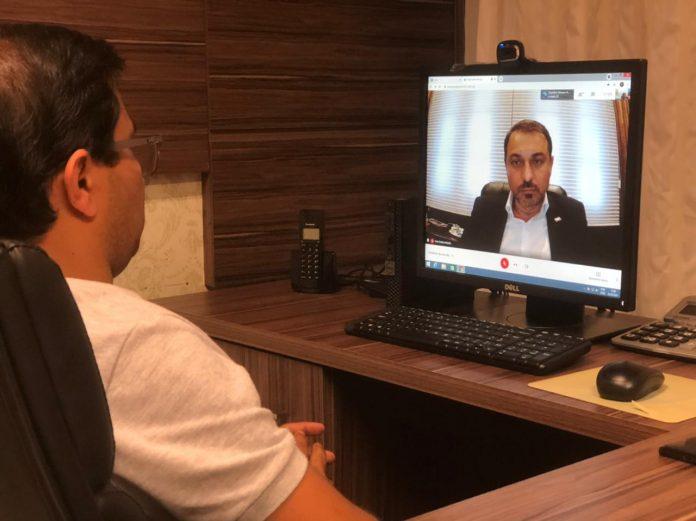 #Pracegover Foto: na imagem há um homem sentado em uma cadeira e um computador