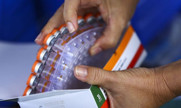 #Pracegover Foto: na imagem há duas mãos e vários frascos de vacina