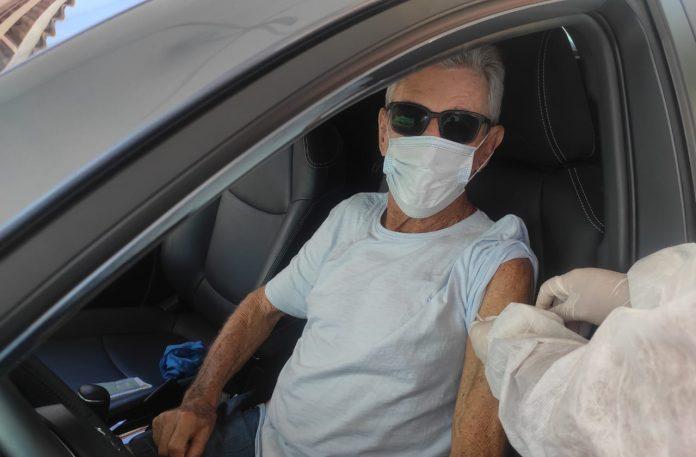 #Pracegover Foto: na imagem há um idoso no carro sendo vacinado