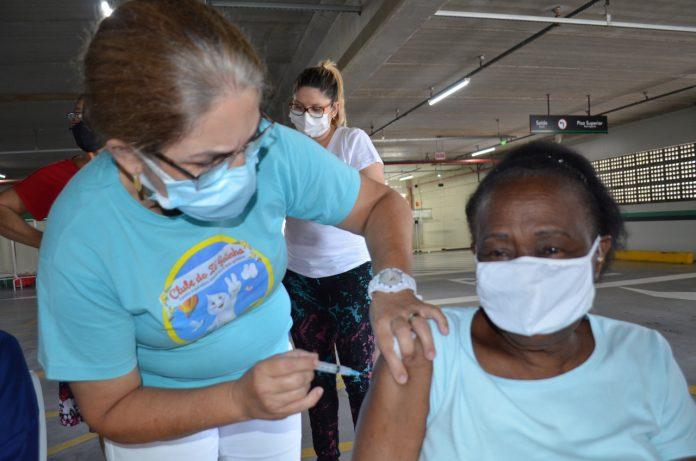 #Pracegover Foto: na imagem há uma mulher aplicando a vacina em uma idosa e há outras duas pessoas aguardando