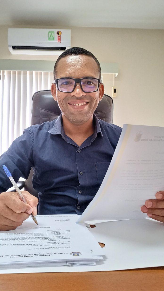 #Pracegover Foto: na imagem há um homem sorrindo, uma caneta e folhas