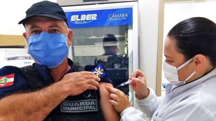 #Pracegover Na foto, um agente da Guarda Municipal sendo vacinado