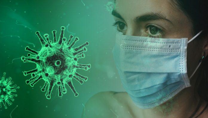 #Pracegover Na foto, mulher aparece usando máscara, ao lado, ilustração de uma célula de coronavírus