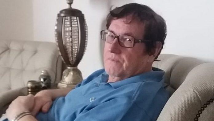 #Pracegover Na foto, Afonso Furghestti aparece sentado em uma cadeira, vestindo uma camisa azul e usando óculos de grau com armação marrom