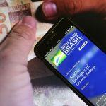#Pracegover Foto: na imagem há duas mãos, um celular e cédulas de dinheiro