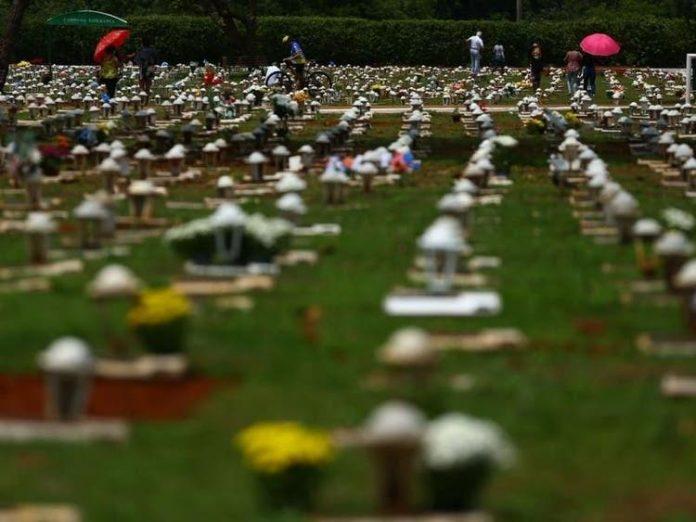 #Pracegover Na foto, cemitério parque com gramado verde e flores sobre os túmulos
