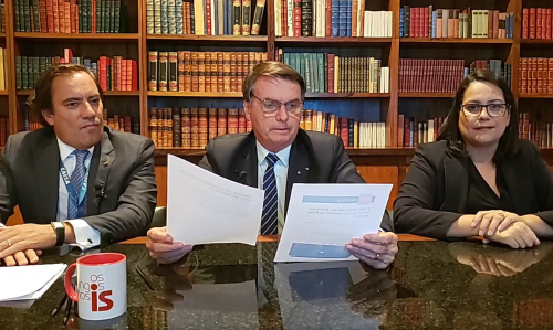 #pracegover Na foto, Bolsonaro aparece sentado sentado, apoiado em uma mesa e acompanhado de outras duas pessoas