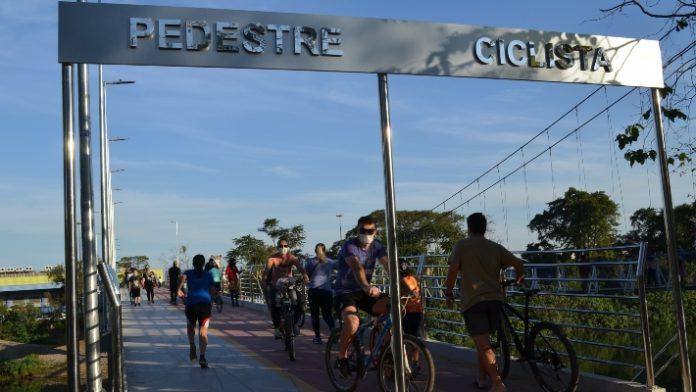 #Pracegover Na foto, pedestres e ciclistas passando pela passarela
